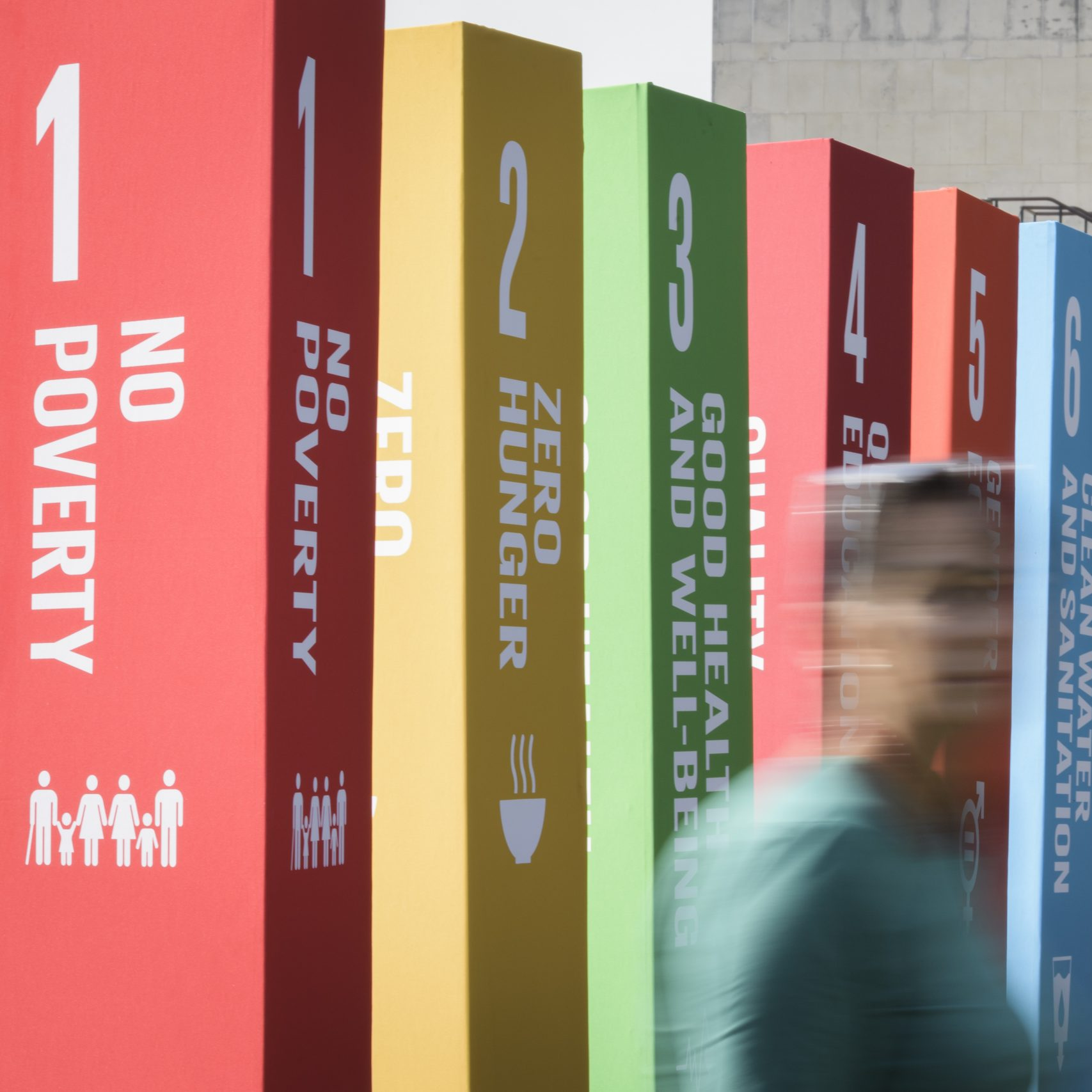 visible are 6 pillars in a range of colours, with the first 5 united nations sustainability goals printed on them