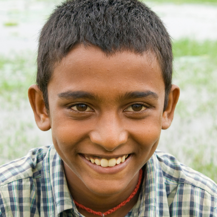 a medium brown skin toned youth with short hair smimling and looking directly a the camera