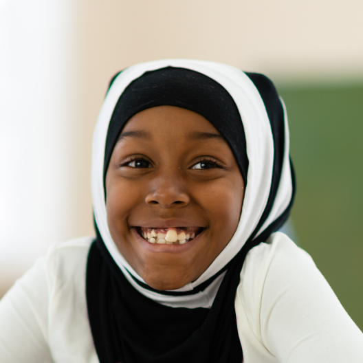 a dark brown skin toned young person in a black and white hijab head dress, smiling directly at the camera